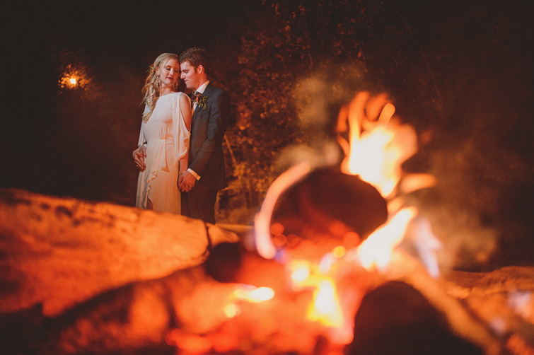bride and groom in front of fire